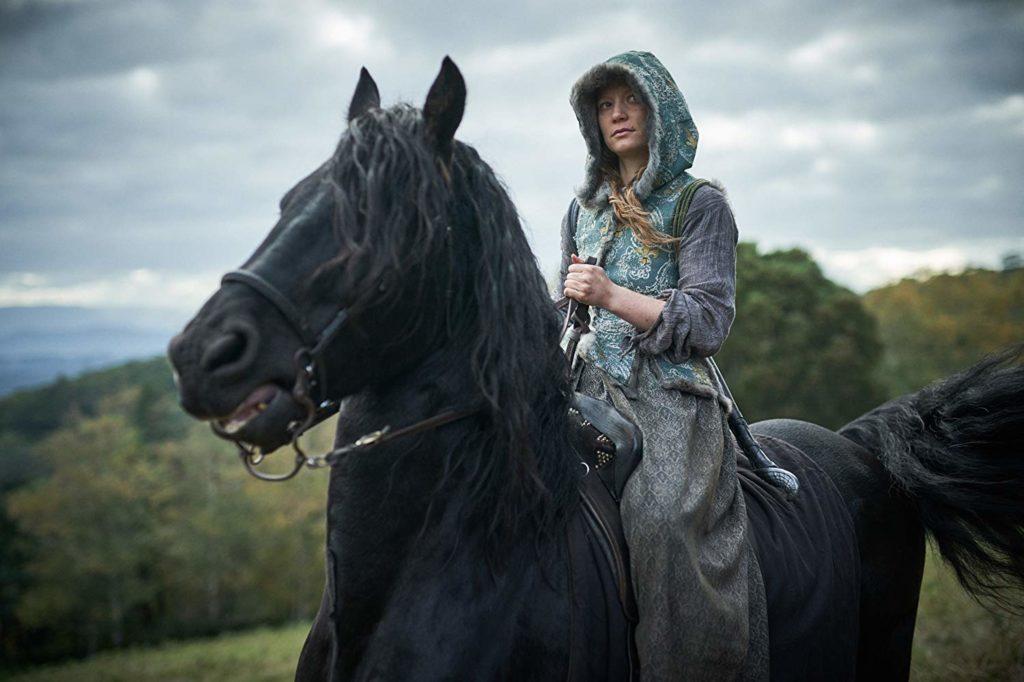 Judy encapuchada y cabalgando un caballo.