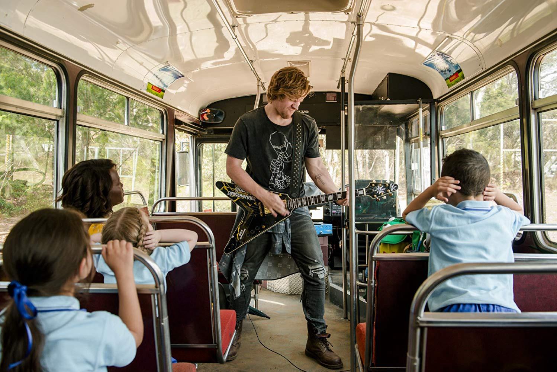 Alexander England tocando la guitarra eléctrica en el autocar infantil de Little Monsters.